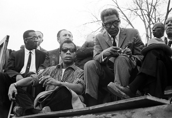 James Baldwin with Bayard Rustin (writing), and A. Philip Randolph, President of the Brotherhood of Sleeping Car Porters. Selma to Montgomery, Alabama Civil Rights March, March 24-26, 1965. Photo by Stephen Somerstein.